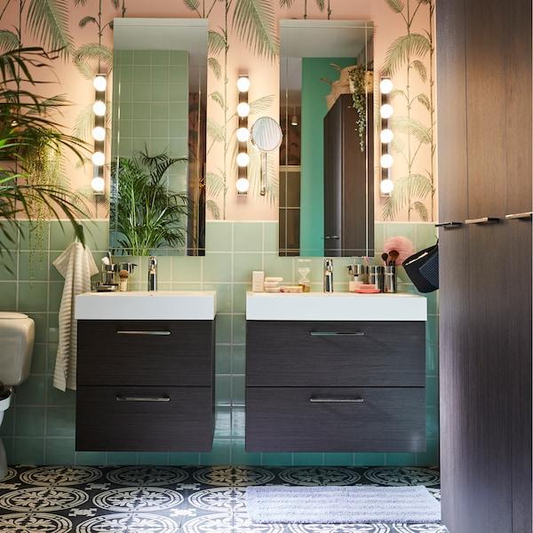 Koupelna se dvěma zrcadly, dvěma umyvadly a úložnými díly a květinami