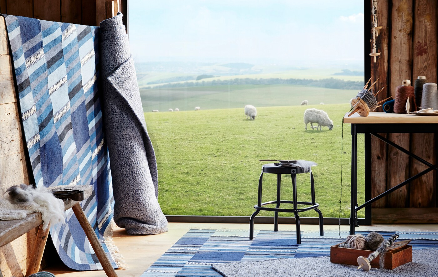 Ковры в сине-серой гамме, лежащие на полу и сложенные в рулон в помещении из дерева, с видом на пасущихся на поляне овец.