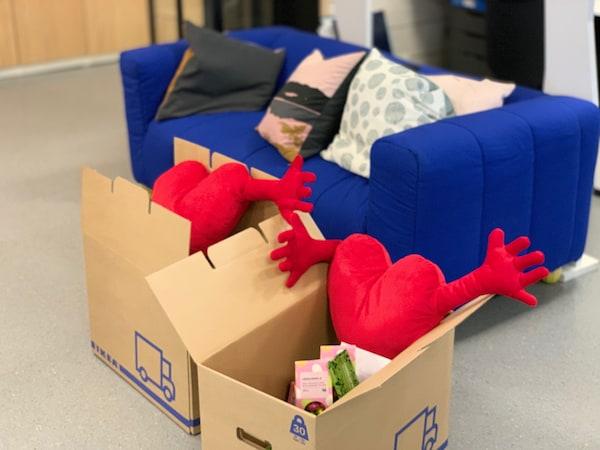 Krabice IKEA s červenými srdíčky a dalšími výrobky, za nimi stojí modré křeslo KLIPPAN.