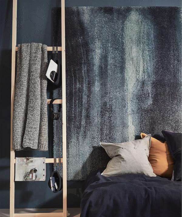 Kraj kreveta, sa spojenim policama koje služe umesto merdevina; knjiga, ćebe, slušalice vise sa letvica.