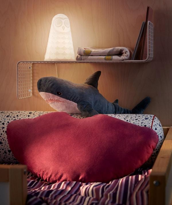 Kraj povišenog kreveta s jastukom i ukrasnim jastukom u obliku dobroćudnog morskog psa i jednostavna zidna polica na kojoj se nalaze noćno svjetlo, knjige i ukras.