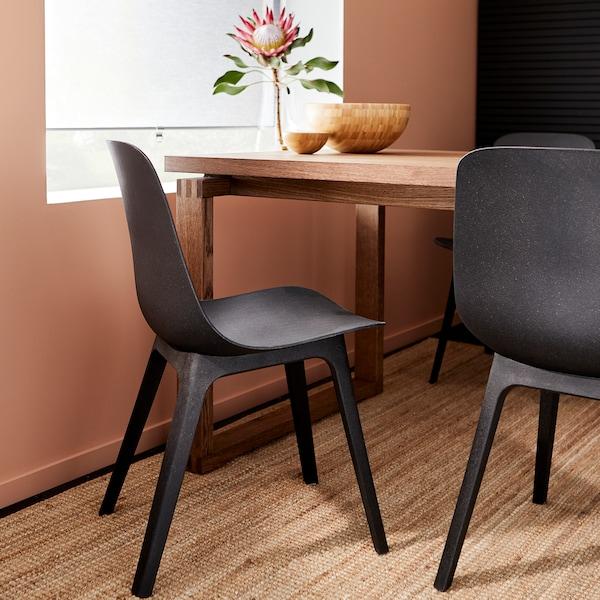 كراسي من الأنتراسايت، وسجادة من الجوت وطاولة من قشرة خشب البلوط المطلي بالبني مع أنية من الخيزران على سطح الطاولة.