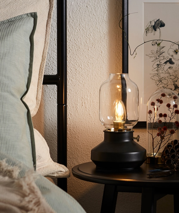Krawędź pościelonego łóżka z wysokim zagłówkiem i postawionymi poduszkami; okrągły stolik nocny z lampą LED w kształcie lampy naftowej.