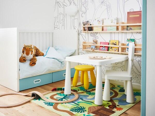 Kreatívne zdobená detská izba s detským nábytkom a rolou papiera LUSTIGT na stene.