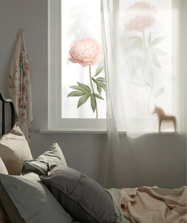 Krevet ispod prozora obasjanog sunčevim svetlom, delimično prekrivenog providnom zavesom i ukrašenog velikim cvetnim stikerima.