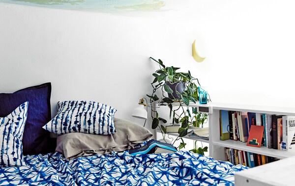 Krevet s plavom posteljinom s uzorkom i police za knjige pokraj njega.