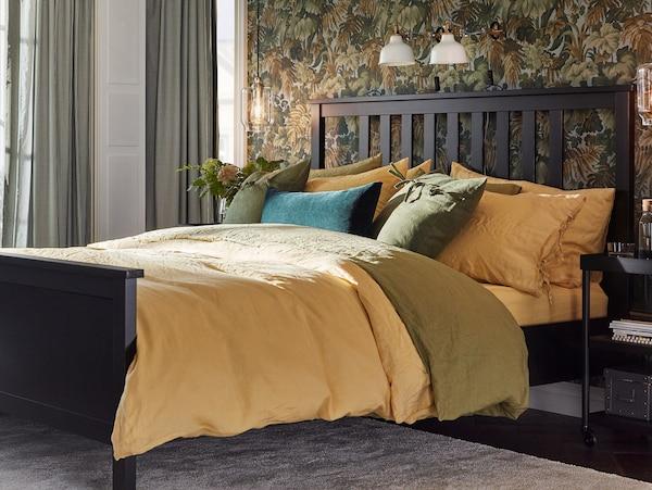 Krevet s PUDERVIVA navlakama i jastučnicama žute i zelene boje, žutom plahtom i ukrasnim jastukom od zelenog baršuna.