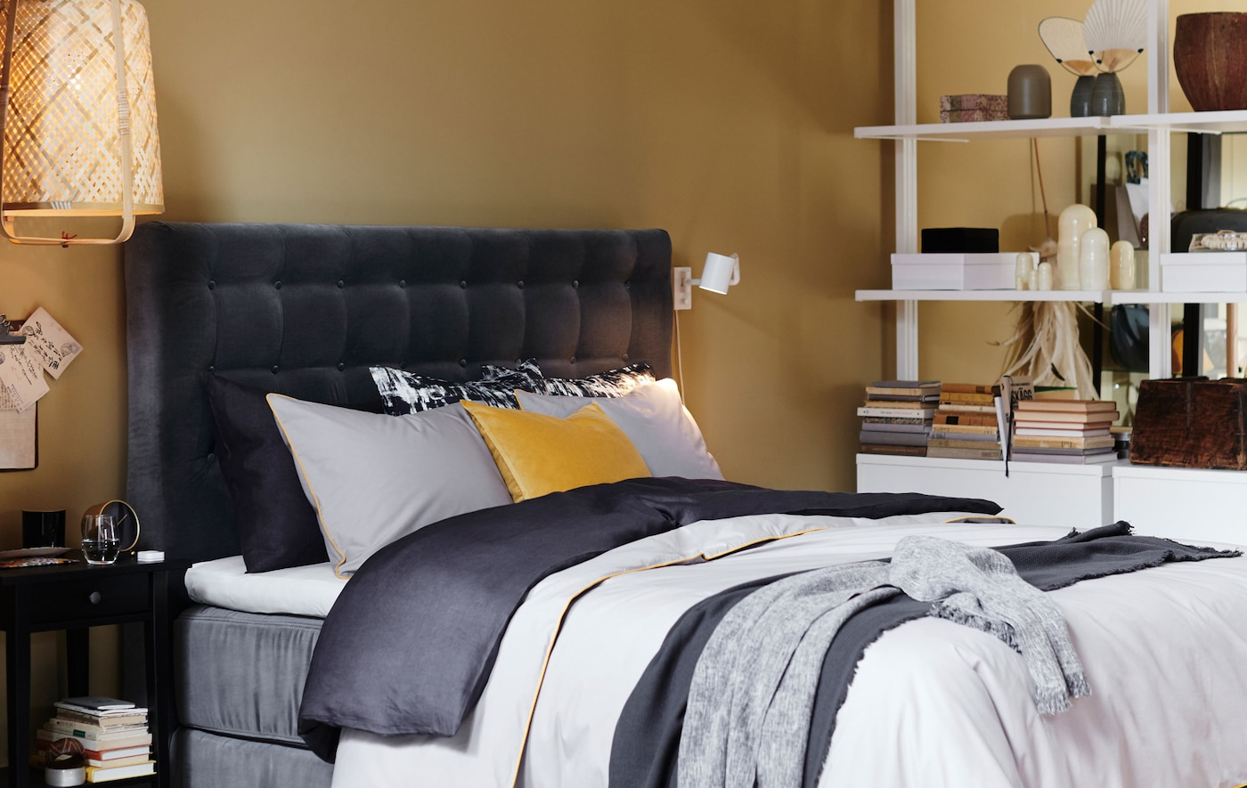 Krevet sa sivim somotnim štepanim uzglavljem i slojevitom posteljinom.