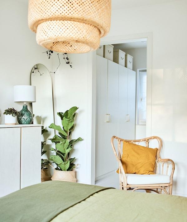 Krevet sa zelenom posteljinom u sobi s pletenom foteljom i pletenom visilicom, i kutkom s belim garderoberima.