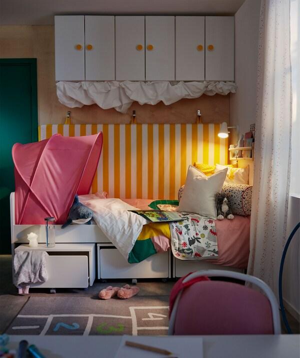 Krevet u uglu dečje sobe. Krevet ima dušek, koji je okačen na zidu iza, i prostor za odlaganje iznad i ispod.