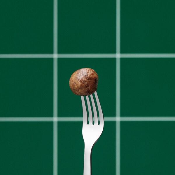 كرة نباتية مطبوخة  من ايكيا في نهاية شوكة فضية عمودية، مقابل خلفية نقش مربعات باللونين الأخضر والأبيض.