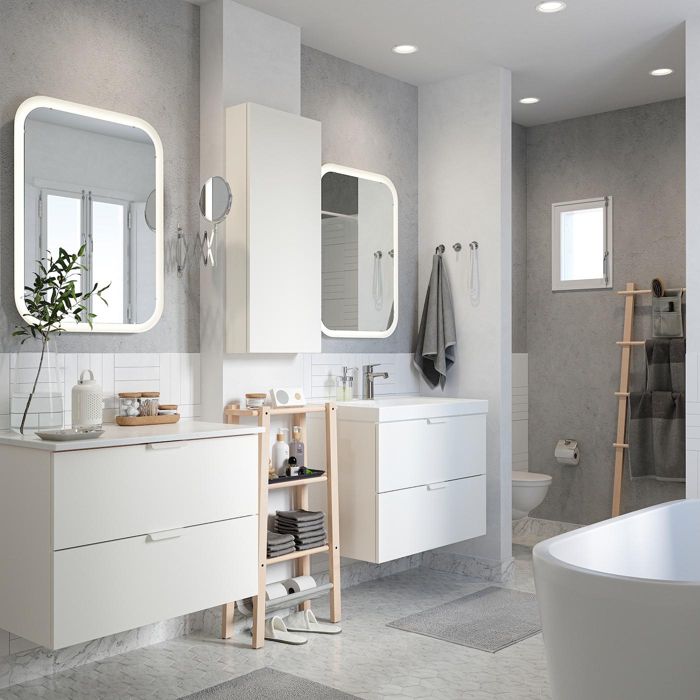 Krispigt vitt badrum med två kommoder, två speglar med integrerad belysning samt badrumsmattor och handdukar i grått.