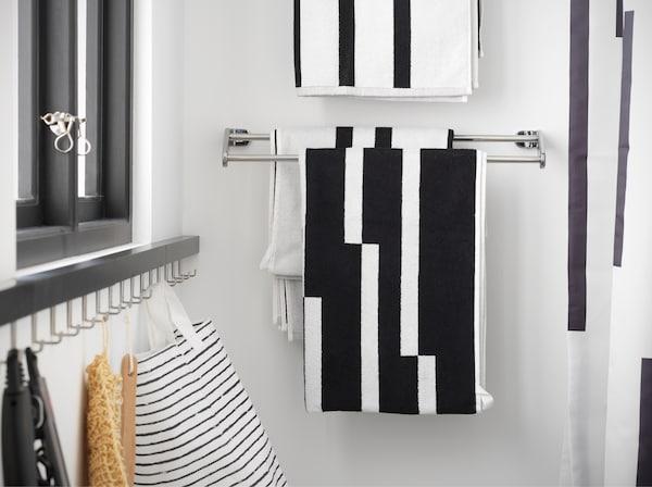 Kromattu pyyhetanko, jossa roikkuu mustavalkoinen raidallinen pyyhe. Se on asennettu suihkun viereen.
