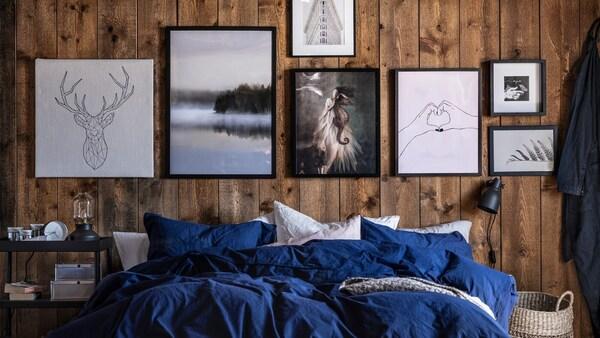 Кровать с бело-синим постельным бельем на фоне деревянных стен, украшенных картинами в черно-бело-серой цветовой гамме.