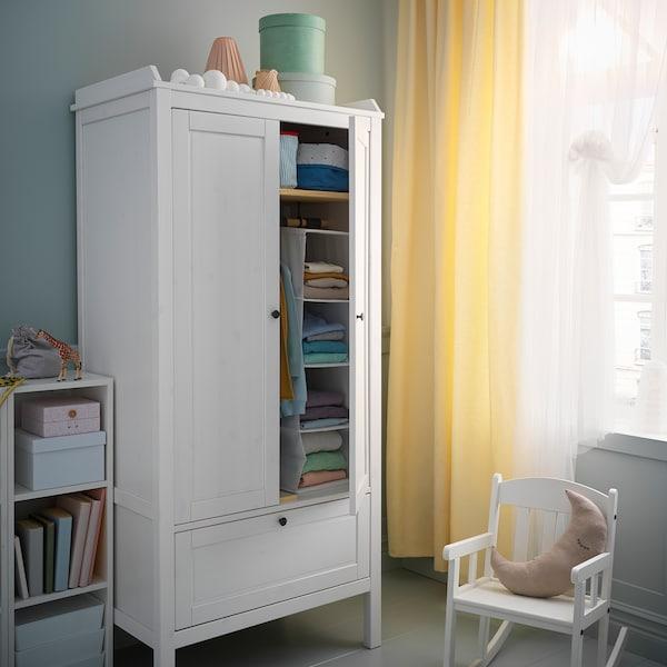 كرسي هزاز ودولاب ملابس بجانب نافذة مع ستائر صفراء. أحد أبواب دولاب الملابس مفتوح، ويظهر الملابس المطوية في الداخل.