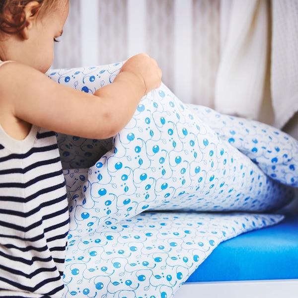 Крупним планом показано малюка, що тримає GULSPARV ГУЛЬСПАРВ білу бавовняну підковдру з візерунком, який нагадує чорницю.