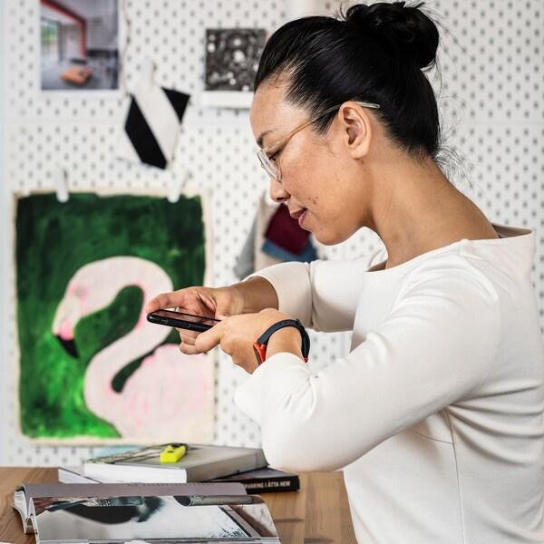 Крупным планом женщина держит смартфон и фотографирует книгу с вдохновившей ее идеей.
