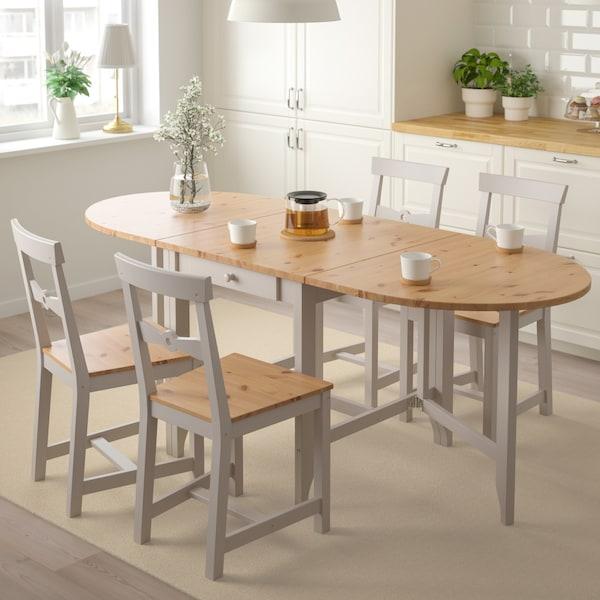 Krzesła GAMLEBY ustawione dookoła stołu GAMLEBY z jasno oświetlonej kuchni z białymi szafkami.