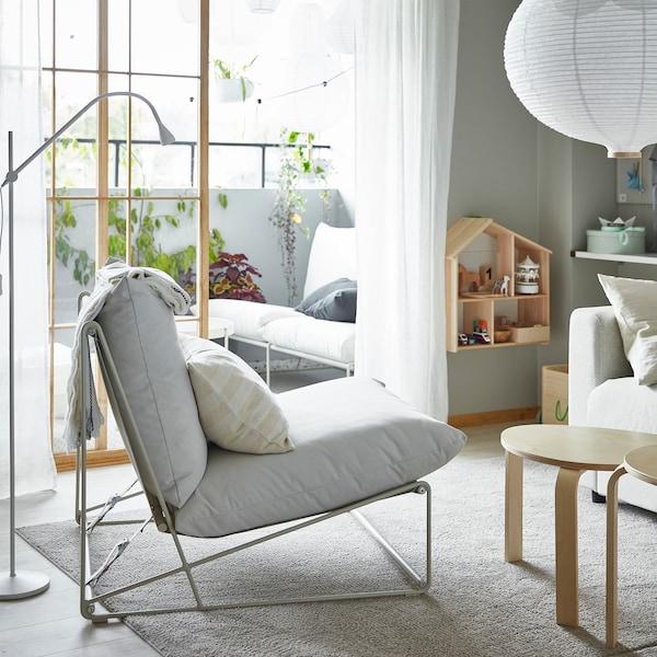Krzesło HAVSTEN w pokoju dziennym i 2-osobowa sofa HAVSTA na balkonie – oba produkty można używać wewnątrz i na zewnątrz.