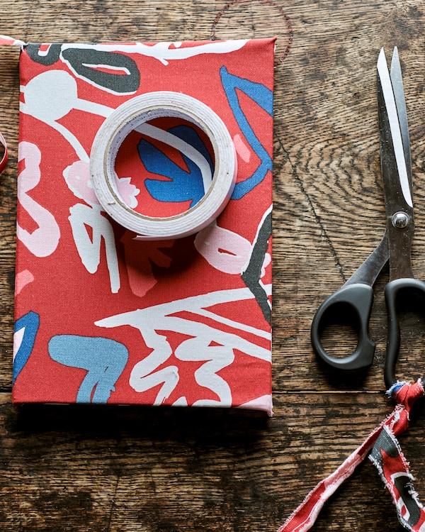 كتابمغطى بقماشأحمرمزركشعلى طاولةخشبيةطراز ريفيمع لفافة من الشريط اللاصق من أعلى، بجوارمقص.