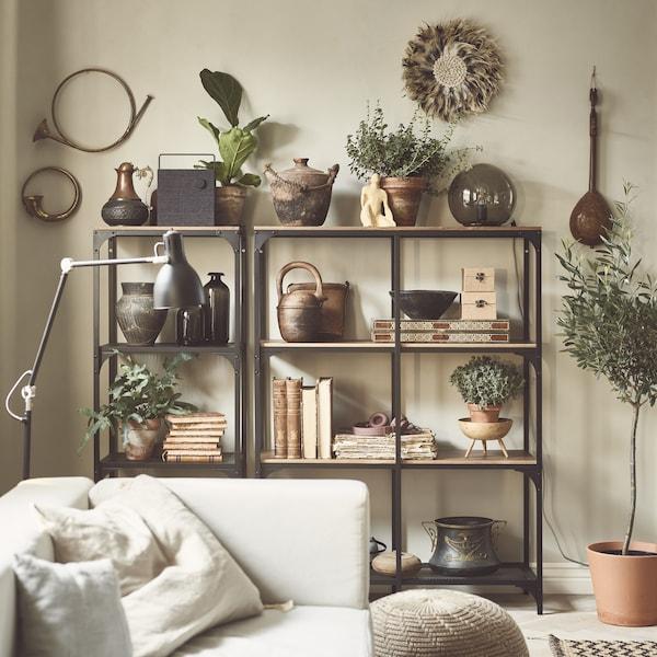 كتب، وأواني ونباتات معروضة على وحدات رفوف خشب ومعدن في غرفة جلوس.