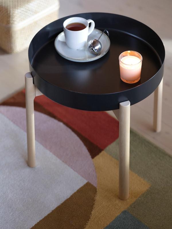 Kubek z herbatą i sitko do zaparzania na stoliku YPPERLIG obok zapalonej świeczki, która tworzy miły nastrój.