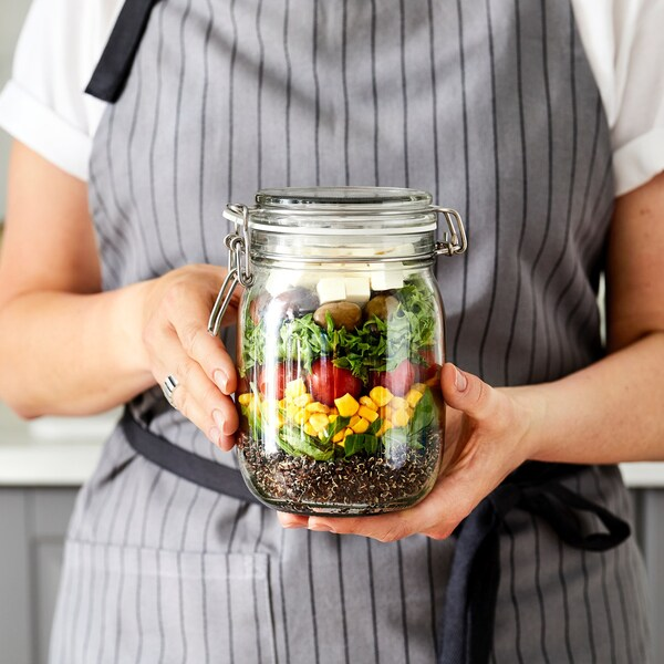 Kuchárka drží poháre KORKEN s uloženými potravinami vnútri.