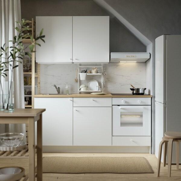 Kuchnia KNOXHULT z białymi frontami i blatem z imitacji drewna i wolnostojącą lodówką.