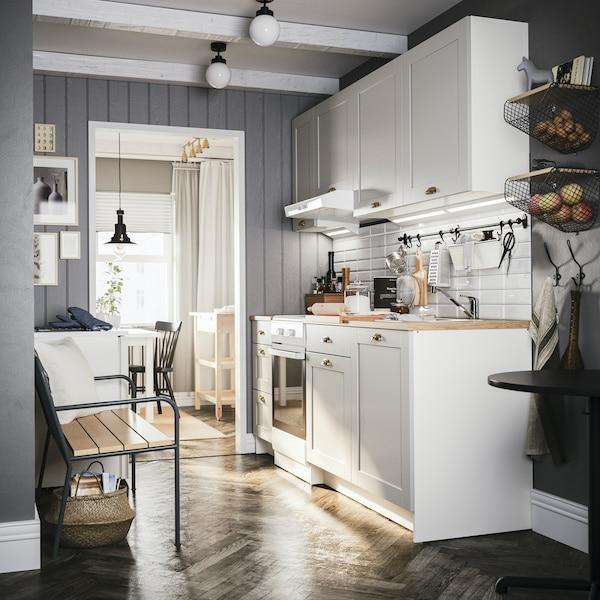 Kuchnia KNOXHULT z szarymi panelami na ścianie i drewnianą podłogą.