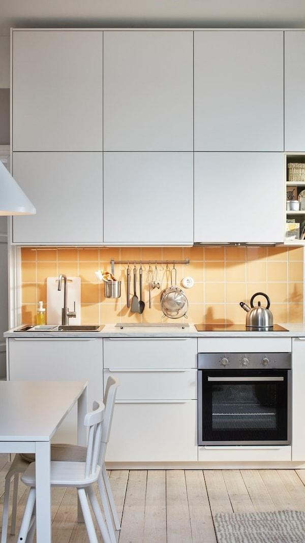 Kuchnia METOD z białymi fronatmi VEDDINGE i pomarańczowymi płytkami na ścianie.