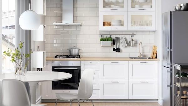 Kuchnia METOD z białymi frontami SÄVEDAL i blatem z imitacji drewna i wolnostojącą lodówką.