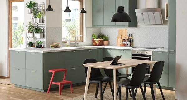 Kuchnia wyposażona w szafki kuchenne z zielonymi frontami