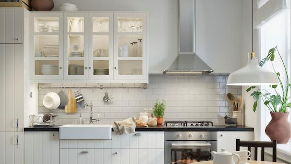Kuchnia z białymi, tradydyjnymi frontami z dużym oknem.