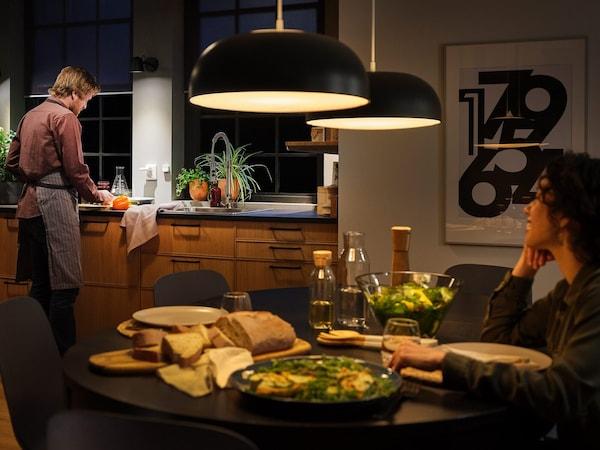 Kuchnia z dużymi lampami wiszącymi z inteligentnym oświetleniem i stół nakryty do kolacji, kobieta siedząca przy stole i mężczyzna stojący przy zlewie.