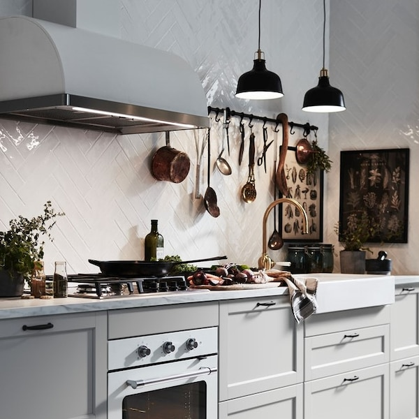 Kuchnia z jasnoszarymi frontami z białymi płytkami na ścianie.
