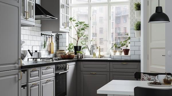 Kuchnia z szarymi, tradydyjnymi frontami z dużym oknem.