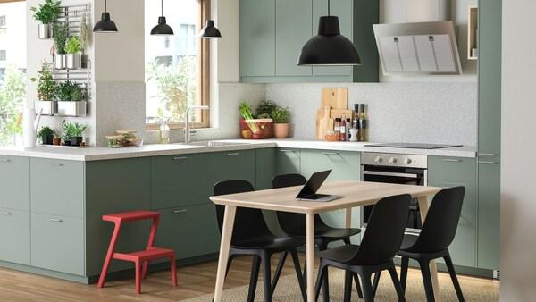 Kuchnia z zielonymi drontami BODARP ze stołem z czarnymi krzesałmi.