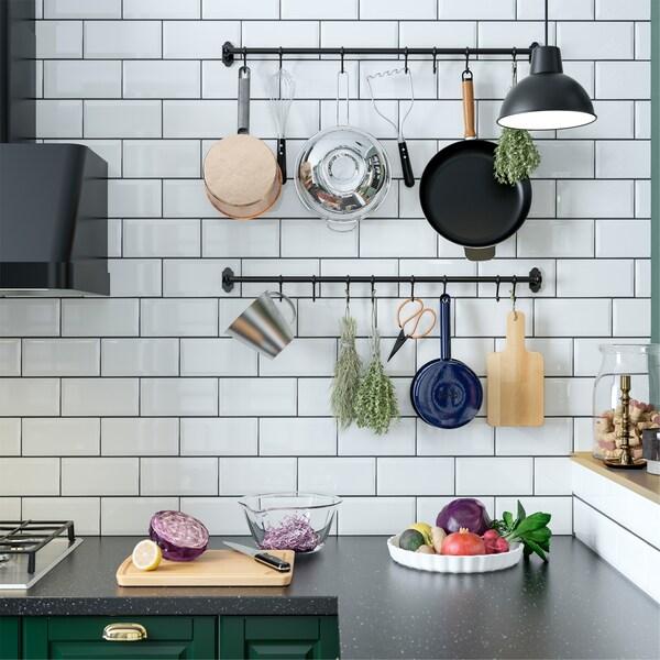 Kuchnia ze ścianą w białych płytkach, z czarnymi drążkami z haczykami, na których wiszą przybory kuchenne i zioła.