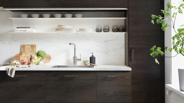 Kuchyňa ASKERSUND s tmavohnedým vzorom jaseňa s doskami na krájanie a zeleninou na pracovnej doske EKBACKEN so vzorom mramoru.