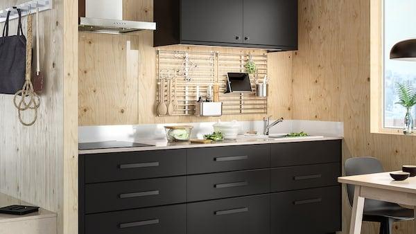 Kuchyňa s antracitovými dvierkami a čelami zásuviek KUNGSBACKA s pracovnou doskou s bielym minerálnym vzorom a drevenými stenami.