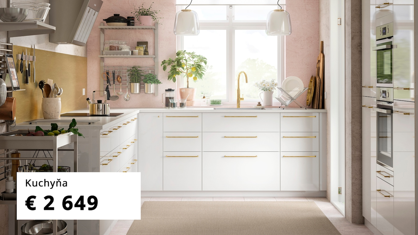 Kuchyňa s ružovou stenou a nástennými policami s kuchynským náčiním a bielymi skrinkami a zásuvkami s doplnkami vo farbe mosadze.