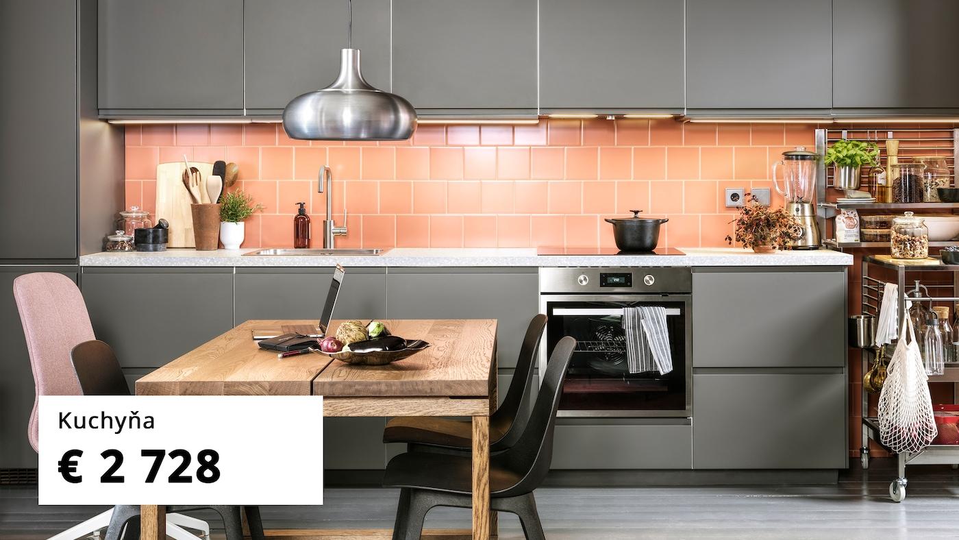 Kuchyňa s ružovým obkladom s tmavosivými čelami kuchynských dvierok a zásuviek, antracitovými stoličkami, jedálenským stolom z dubovej dyhy a závesnou lampou VÄXJÖ.