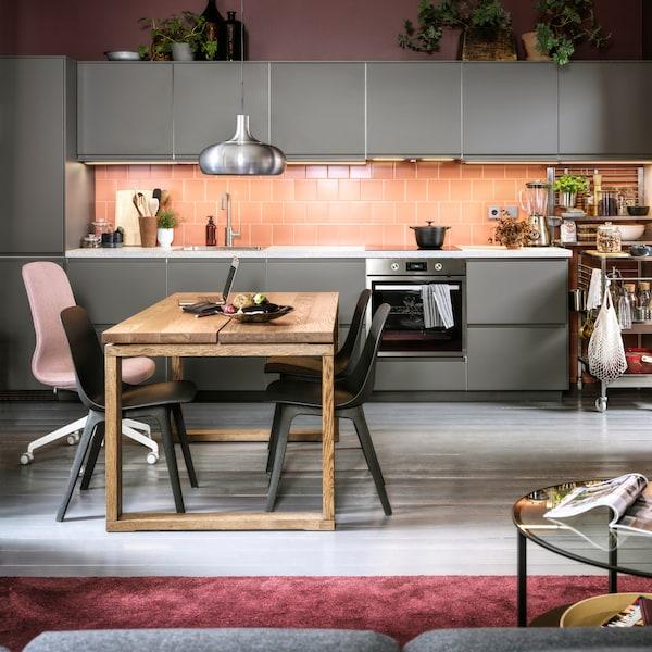 Kuchyňa s ružovým obkladom s tmavosivými dvierkami a čelami zásuviek, antracitovými stoličkami, jedálenským stolom z dubovej dyhy a závesnou lampou VÄXJÖ.