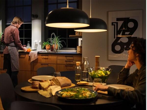 Kuchyňa s veľkými závesnými lampami s inteligentným osvetlením a stolom na večeru, žena sedí pri stole a muž pri dreze.