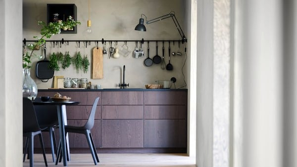 Kuchyňa so stolom a stoličkami SINARP a nástennou tyčou HULTARP s háčikmi.