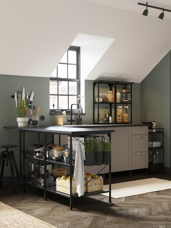 Kuchyně ENHET s šedými dvířky a čely zásuvek a antracitovými rámy v mechově zelené místnosti s hrnci a pánvemi v otevřeném úložném prostoru.
