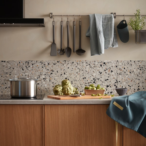 Kuchyně s nástěnnými lištami, na pracovní desce jsou připravené suroviny k vaření.