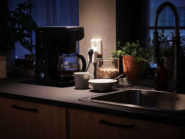 Kuchyňská linka s kávovarem zapojeným do bezdrátové ovládací zásuvky.