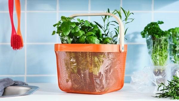 Kuchynská pracovná doska s bylinkami v oranžovom koši RISATORP z oceľovej sieťoviny s rúčkou z brezovej dyhy.