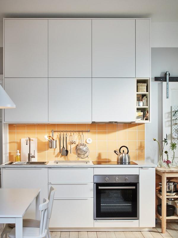 Kuchyňská pracovní deska s dřezem, deskou a náčiním, nad a pod ní jsou bílé skříňky METOD.